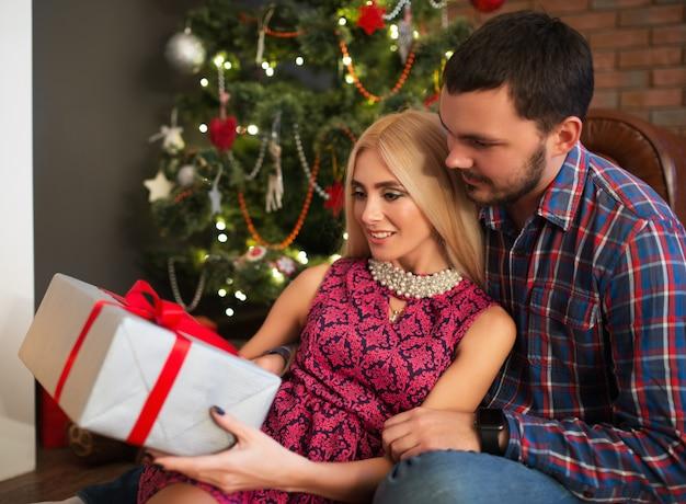 Bella giovane coppia una ragazza affascinante e un ragazzo che tiene una scatola con un regalo