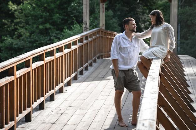 Una bella giovane coppia comunica su un ponte nella foresta, un appuntamento nella natura, una storia d'amore.