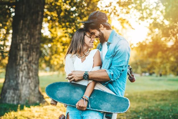 Bella giovane coppia godendo, baciando e abbracciando all'aperto nel parco di skateboard della città.