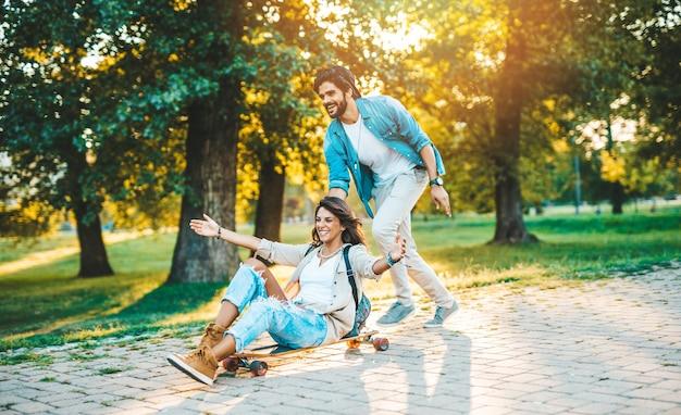 Bella giovane coppia godendo all'aperto nel parco di skateboard della città.