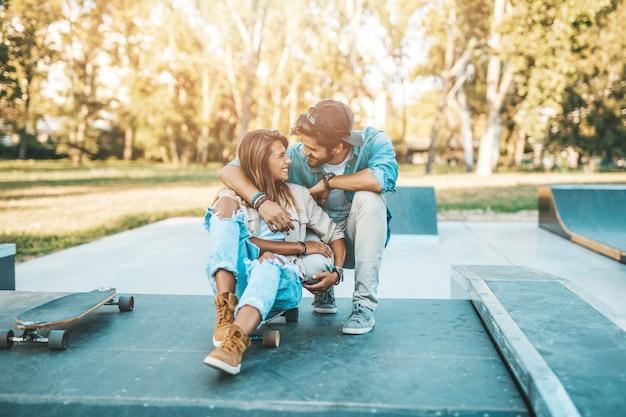 Bella giovane coppia che si diverte all'aperto nel parco dello skateboard della città