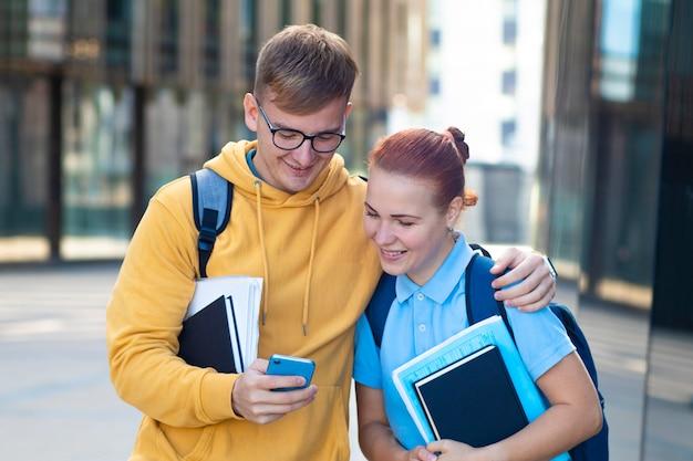 Bella giovane coppia, studenti felici con libri, libri di testo in piedi insieme all'aperto.