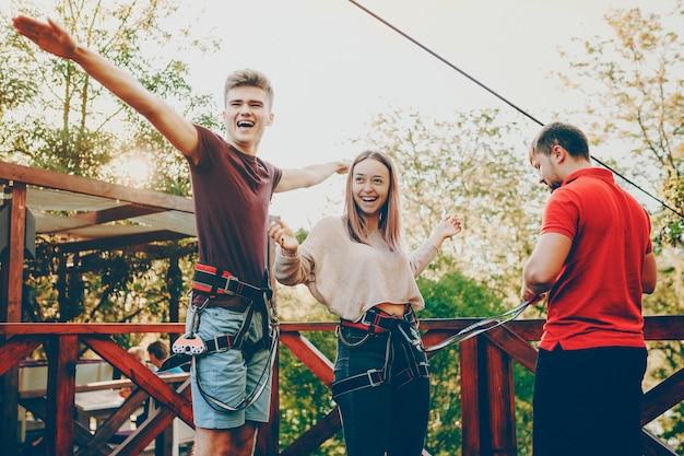 Belle giovani coppie divertendosi a ridere mentre si prepara a saltare con lo scivolo di corda durante il viaggio.