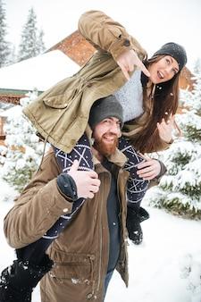 Bella giovane coppia che si diverte e mostra il gesto rock in inverno
