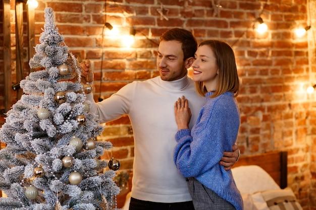 Bella giovane coppia a casa che decora un albero di natale