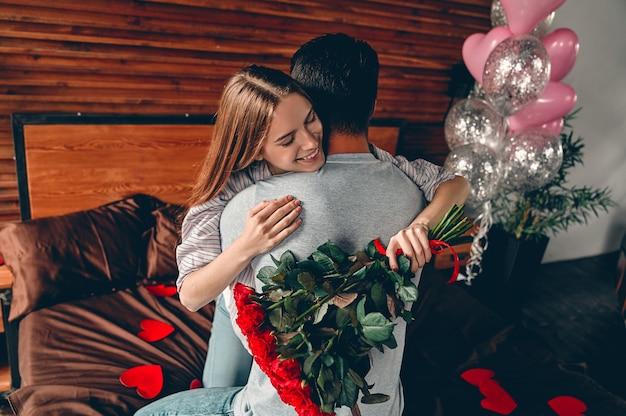 Bella giovane coppia a casa. abbracciare, baciare e godersi il tempo insieme mentre si celebra san valentino con rose rosse e mongolfiere.