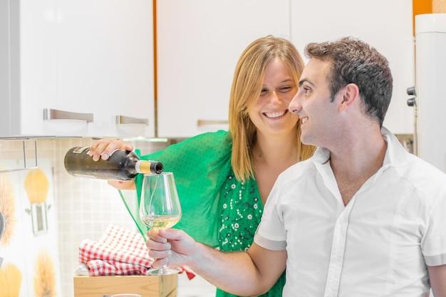 Bella giovane coppia sta bevendo vino e sorridendo in cucina a casa