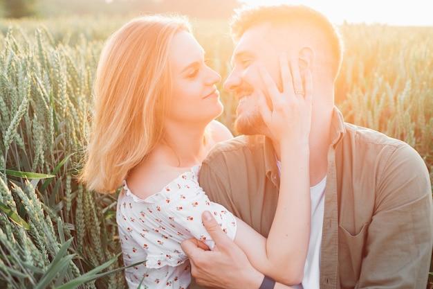 La bella giovane coppia è felice di stare insieme la sera d'estate sotto i raggi del sole al tramonto. amore e tenerezza. bei momenti di vita. giovinezza e bellezza. pace e disattenzione.