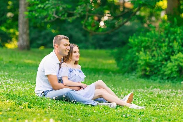 La bella giovane coppia si sta divertendo seduta sull'erba nel parco abbracciata guardando in lontananza