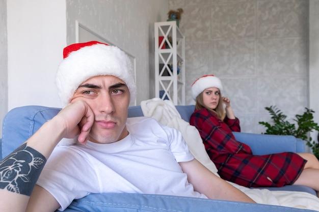 Bella giovane coppia sta litigando a natale mentre era seduto sul divano di casa.