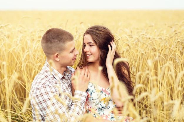 Bella giovane coppia sta riposando su un campo di grano