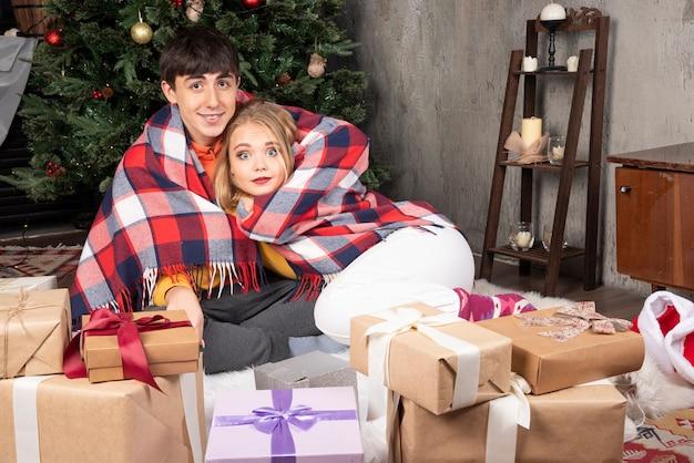Una bella giovane coppia è avvolta in una calda coperta all'interno di casa.