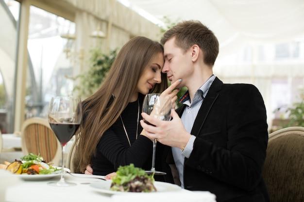 Bella giovane coppia che si bacia al ristorante