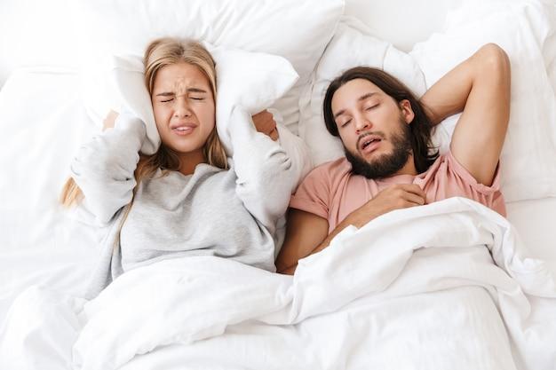 Bella giovane coppia sdraiata a letto a casa, donna infastidita contro le orecchie con il cuscino