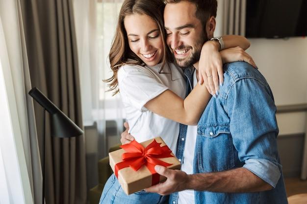 Bella giovane coppia innamorata a casa, che festeggia con uno scambio di scatole regalo, si abbraccia