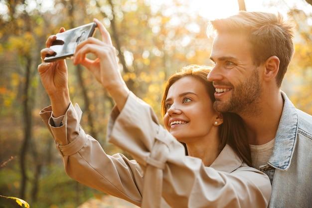 Bella giovane coppia innamorata che usa il cellulare mentre trascorre del tempo al parco autunnale, facendo un selfie