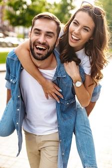 Bella giovane coppia innamorata che cammina all'aperto per la strada della città, cavalcata sulle spalle
