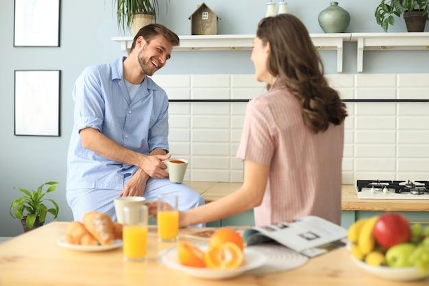 Bella giovane coppia in pigiama si guarda e sorride mentre cucina in cucina a casa.