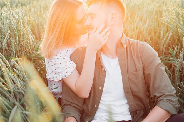 La bella giovane coppia irradia una tenerezza sconfinata l'una per l'altra seduti in campo tra l'erba alta. amore e tenerezza. bei momenti di vita. giovinezza e bellezza. pace e disattenzione.