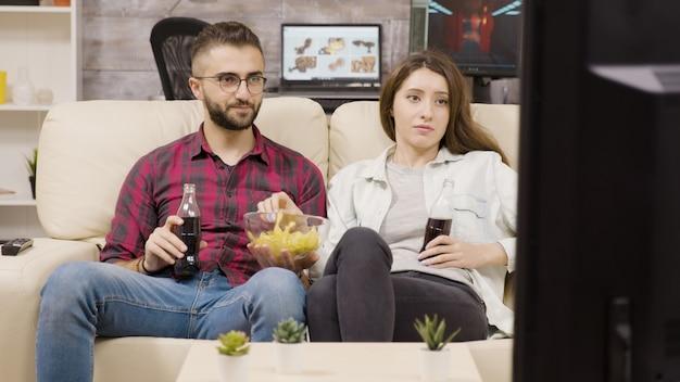 Bella giovane coppia seduta sul divano godendo di patatine e soda mentre si guarda la tv di notte.