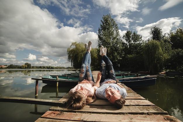 Belle giovani coppie e sorridere mentre trovandosi sul molo