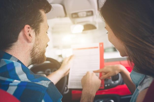 Bella giovane coppia in piedi presso la concessionaria scegliendo l'auto da acquistare.