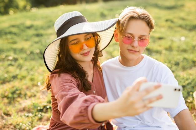 La bella giovane coppia con gli occhiali da sole viene fotografata al telefono