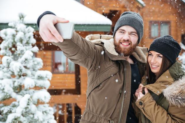 Bella giovane coppia che prende selfie in inverno