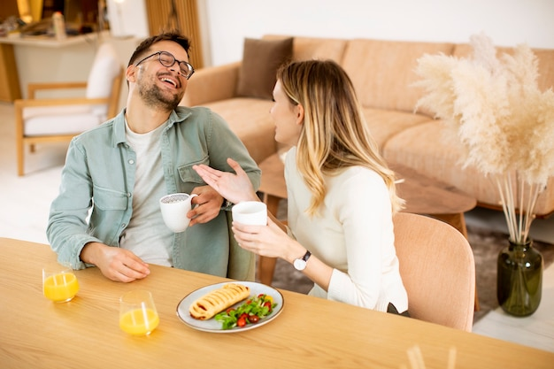 Belle giovani coppie che parlano e sorridono mentre mangiano sano a casa.