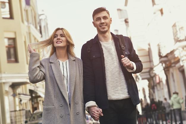 Belle giovani coppie che camminano alla ragazza della via che gioca con i suoi capelli