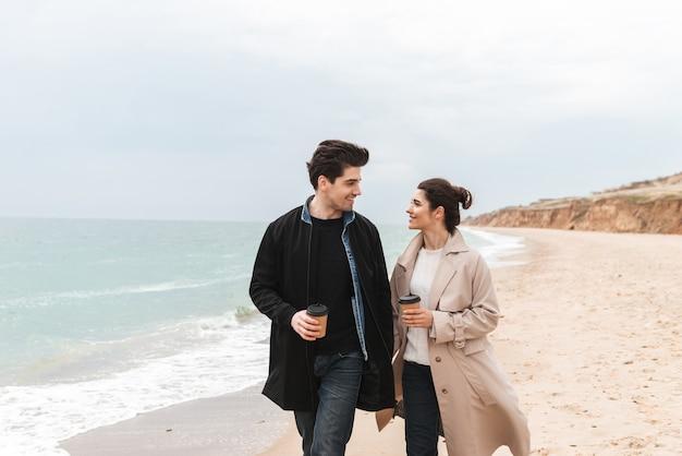 Bella giovane coppia che indossa cappotti camminando in spiaggia, bevendo caffè da asporto
