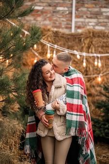 Una bella giovane coppia in abiti bianchi è seduta vicino a un albero di natale in giardino. uomo e donna felici, romanticismo, festa di natale, divertimento, amore.