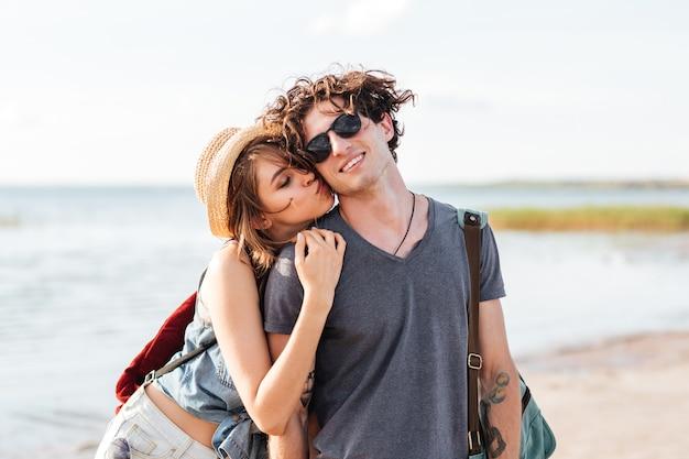 Bella giovane coppia con zaini in piedi e baciare sulla spiaggia