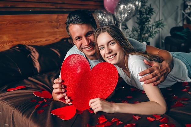 Bella giovane coppia con un grande cuore rosso nelle loro mani in camera da letto è sdraiato sul letto e abbraccia