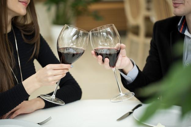 Bella giovane coppia con bicchieri di vino rosso in un ristorante di lusso