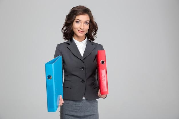 Bella giovane donna felice riccia in vestito grigio che tiene raccoglitori rossi e blu