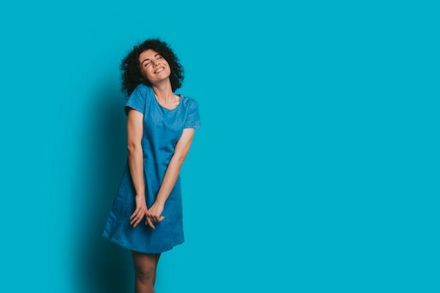 Bella giovane donna riccia che ride con gli occhi chiusi contro una parete blu dello studio vestita in abito blue jeans.