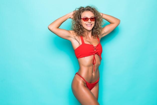 Bella giovane donna riccia in occhiali da sole e costume da bagno rosso su una parete verde