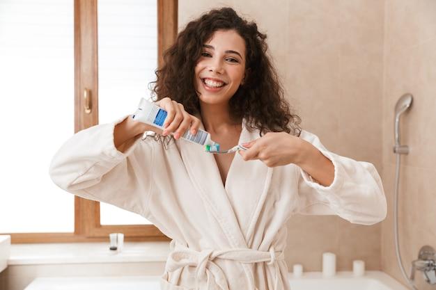 Bella giovane donna carina in bagno spazzolatura pulizia dei suoi denti.