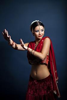 Bella giovane donna che balla in abiti tradizionali indiani