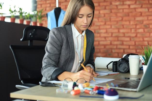 Bella giovane designer che prende appunti mentre è seduta nel suo studio.