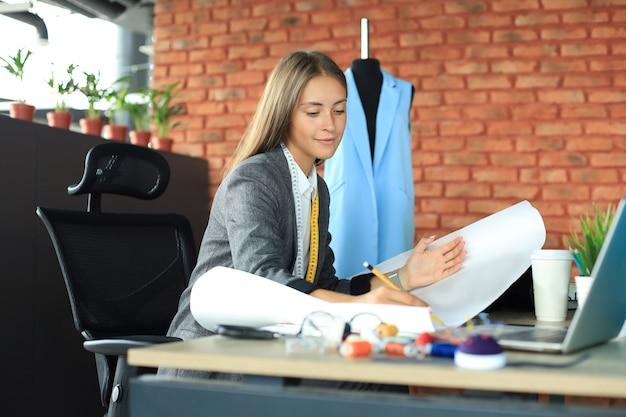 Bella giovane designer che lavora su schizzi mentre è seduta nel suo studio.
