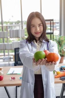 Una bellissima giovane dottoressa ha sorriso agli asiatici mostrando vitamina frutta in un ufficio moderno con una grande vetrata.