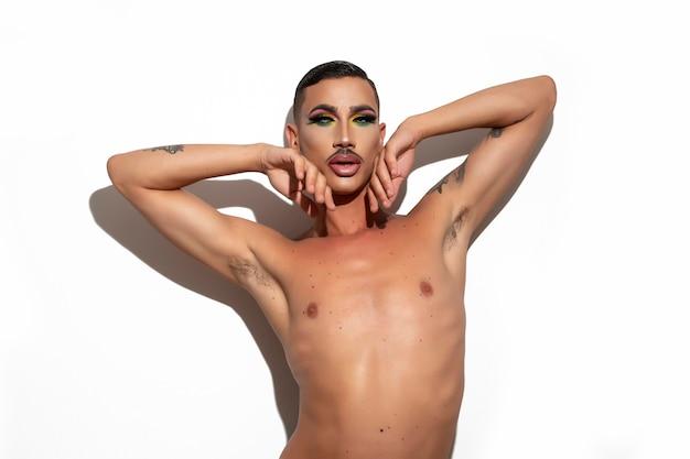 Bella giovane drag queen con capelli corti e baffi con trucco guardando la telecamera con sfondo bianco