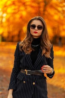 Bella giovane donna d'affari elegante con occhiali da sole vintage in un blazer alla moda con un maglione cammina in un parco con foglie di autunno colorate arancioni al tramonto. stile e bellezza autunnali femminili
