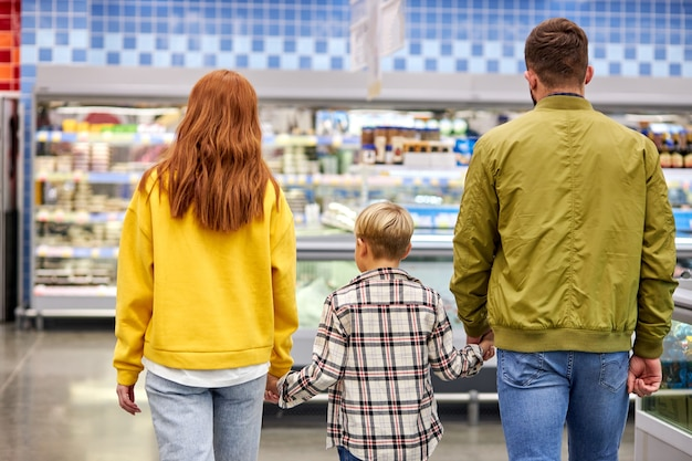 Bella e giovane famiglia facendo shopping insieme