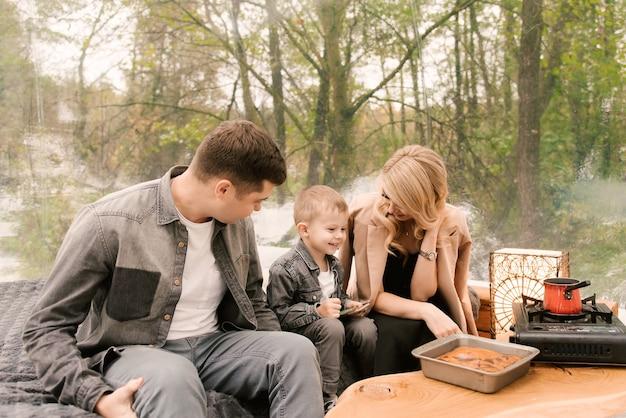 Figlio e donna giovane e bella famiglia uomo rilassarsi nella foresta in natura in una grande tenda rotonda con un letto e una stufa per cucinare, picnic, campeggio