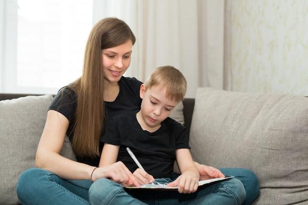 Bella giovane madre di famiglia e figlio fanno lezioni di compiti