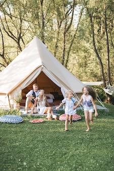 Bella giovane famiglia di trascorrere del tempo insieme nel parco o prato estivo