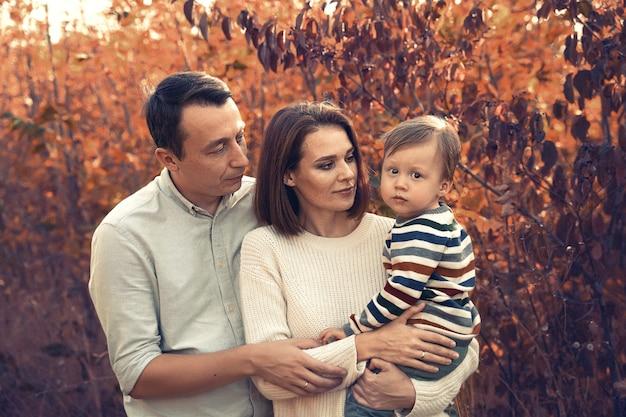 Bella giovane famiglia con un bambino piccolo in una passeggiata autunnale
